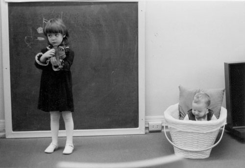 A girl plays the violin with a young spectator nearby. Photo from the Bradley Institute collection.