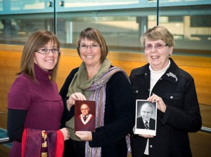 Three generations of Brock women: (left to right) Kate Dirks (MA '12), Linda Dirks (BA '84), Patricia Waters (BA '88) with the graduation sash and photo of Lou Cahill (LLD '91), and James Waters (BA '77)