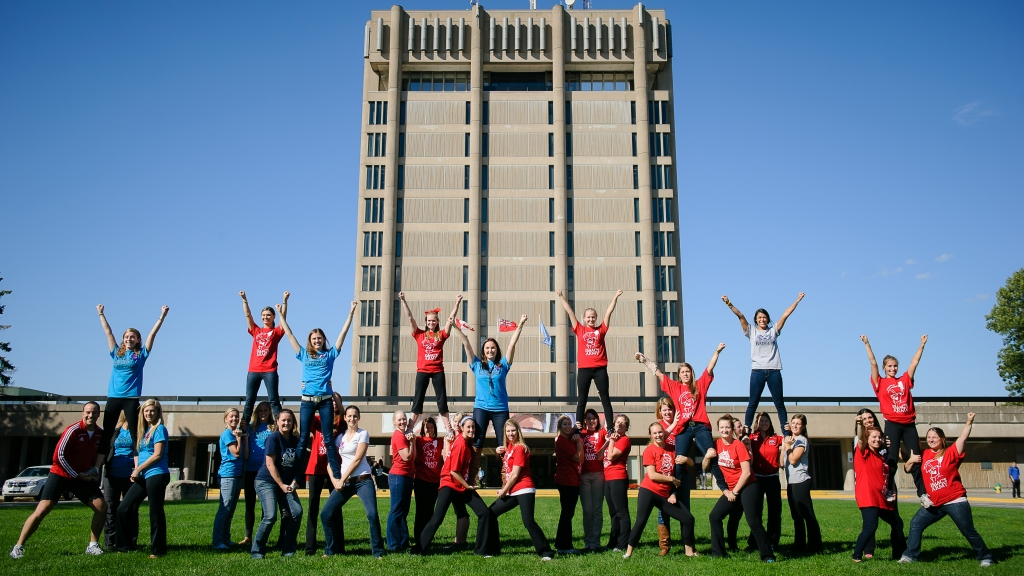 Brock cheerleaders posing in front of the Schmon Tower during their generational reunion.