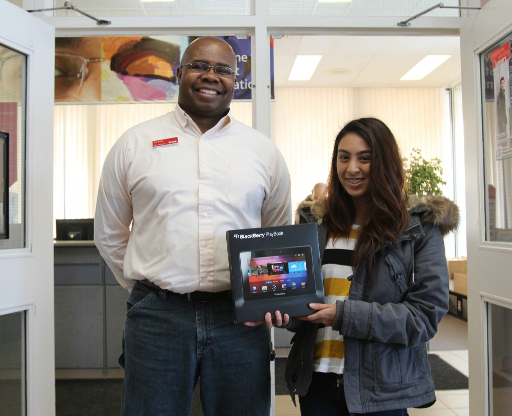 Amira Abdelhamid, a first-year neuroscience student, receives a new BlackBerry Playbook tablet from Troy Brooks, academic integrity officer.