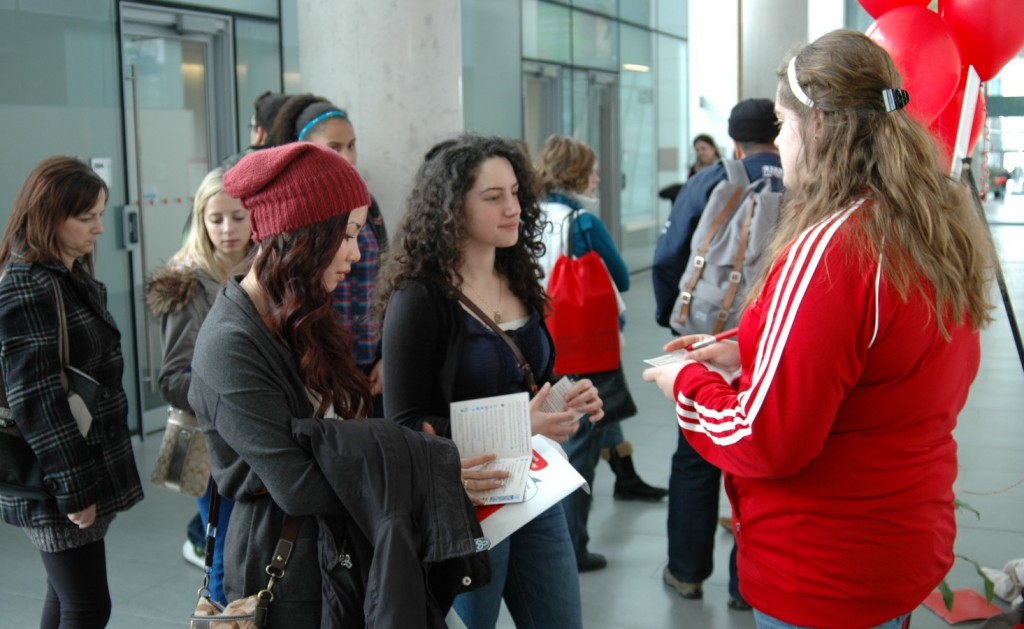 Prospective students Helen Le (red cap) and Nour Alideeb, attending from Mississauga, chat with guide Victoria Maxmen on Sunday.