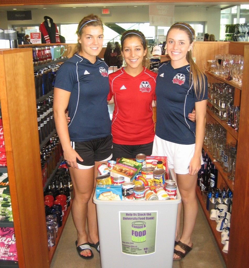 Student athletes Beth Hone, Arian Falasca and Jessica Bagnulo show off some of the haul collected during the Student Justice Centre's food drive to fill the campus food bank, which runs until Aug. 23.