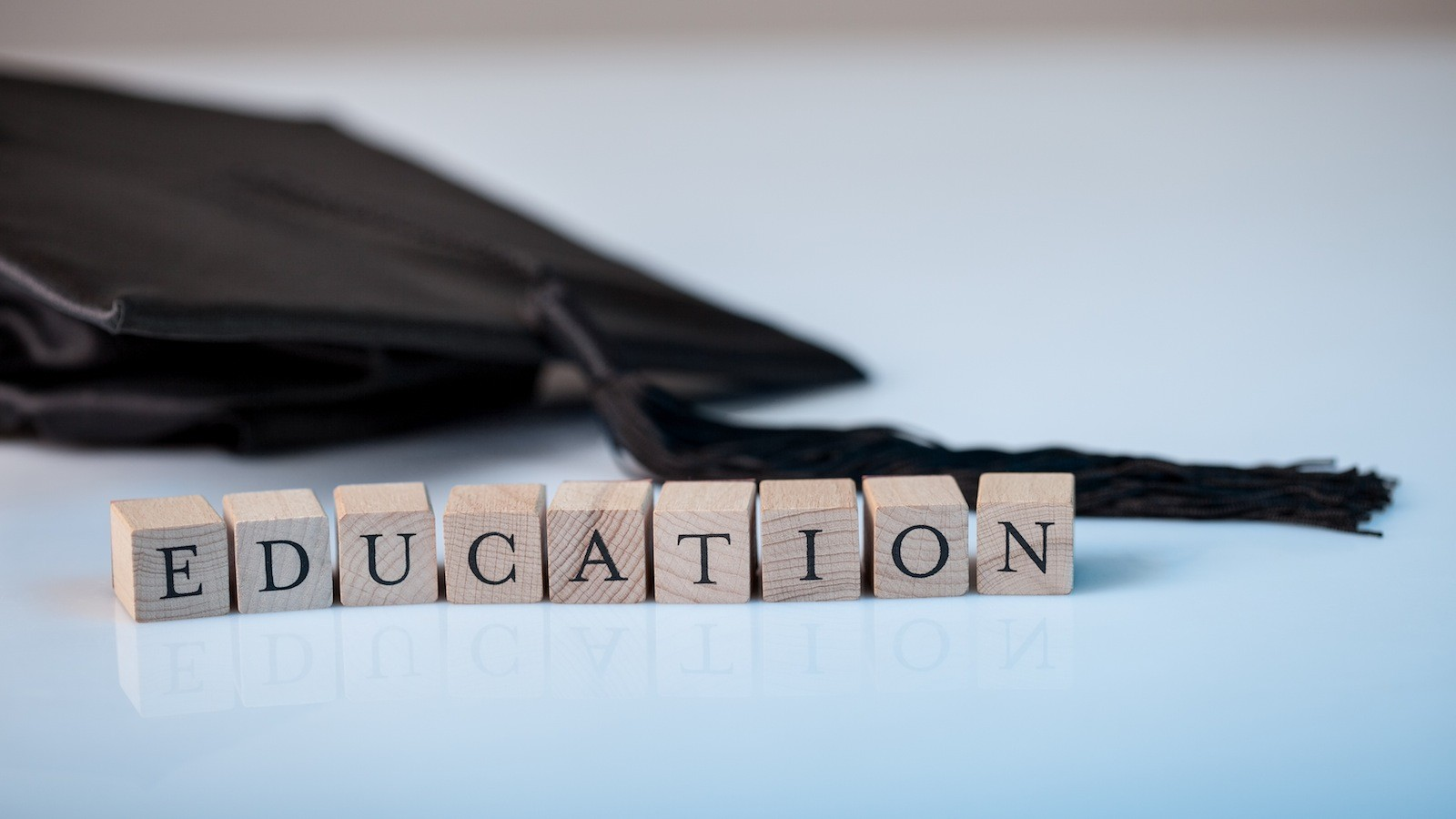 Education concept with the alphabet letters for Education spelt out on wooden blocks beside a graduation cap