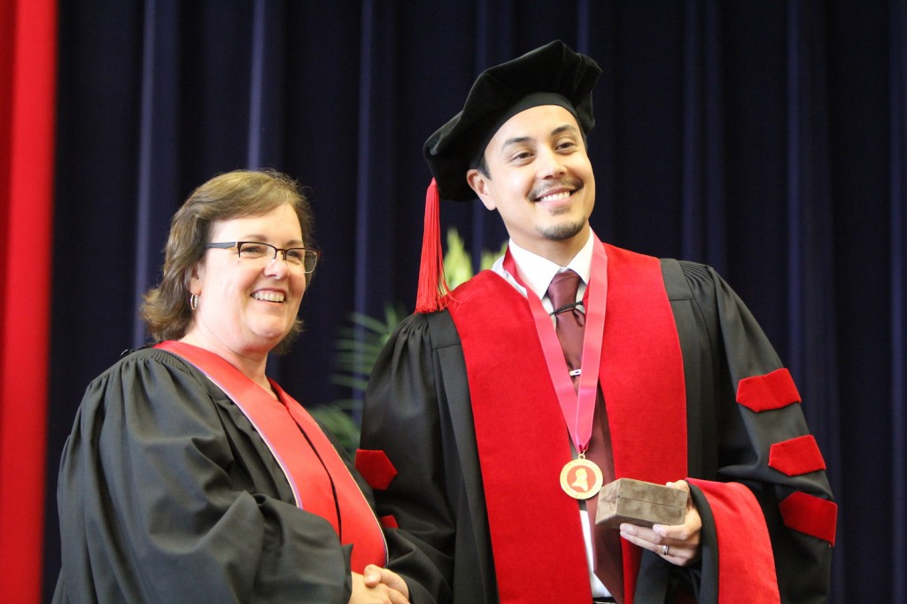 Paul Adachi, who graduated with his PhD in psychology, receives the Spirit of Brock medal from Kristine Freudenthaler of the Board of Trustees at Tuesday afternoon's convocation ceremony.