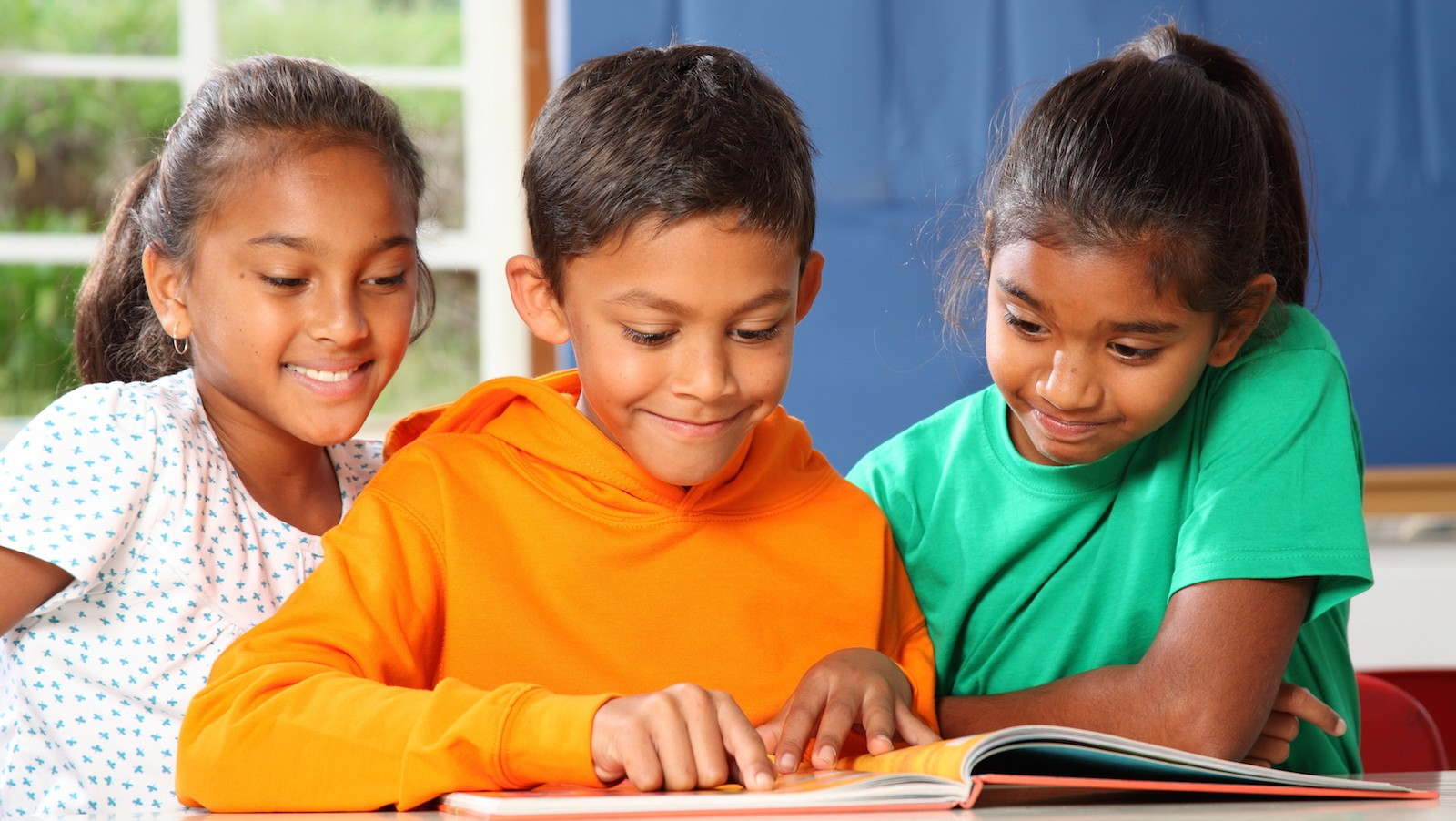 Cheerful young primary school children reading and learning together in the classroom