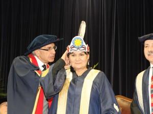Ned Goodman helps adjust Chancellor Shirley Cheechoo's crown.