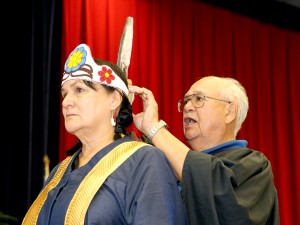 Chancellor Shirley Cheechoo is given a beaded crown with an eagle's feather by her older brother Ben Saturday during her installation ceremony.