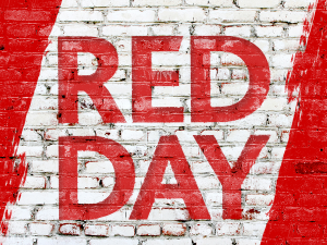 "Brick wall with the words ""Red Day"" in red paint."