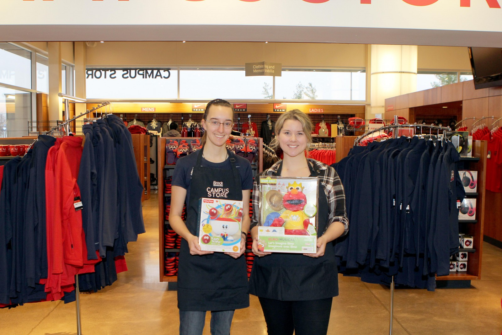 Campus store employees Laurie Taylor, left, and Hayley Clifford show off some of the gifts donated for Community Care.