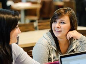students talk in a classroom