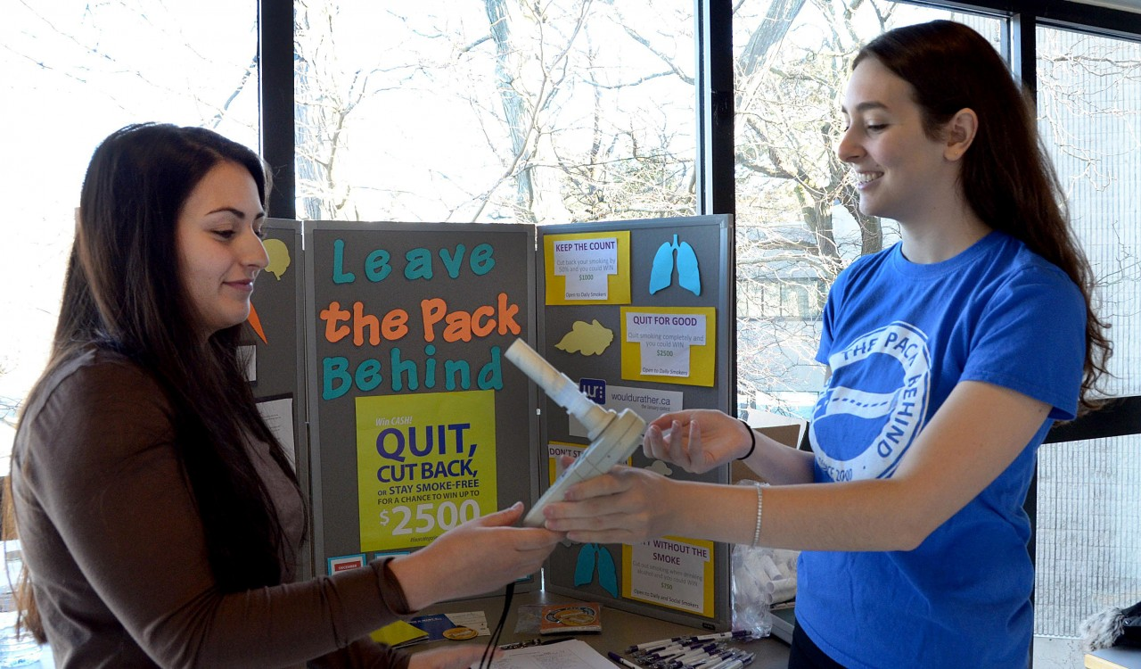 Isabella Churchill, Campus Coordinator for Leave the Pack Behind is teaching student volunteer Andrea Sacco how to show students the correct way to use and read the results of the LTPB carbon monoxide detector, a teaching tool which measures the carbon monoxide levels in a person's lungs.
