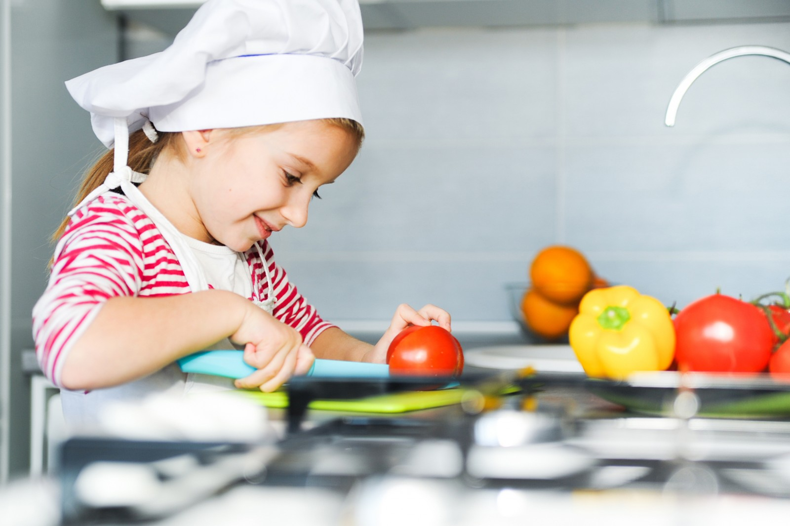 A young girl in a chef's hat chops vegetables