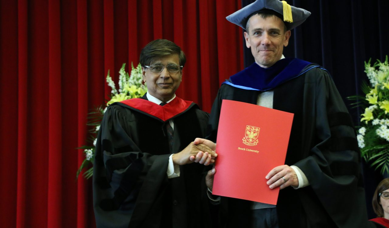 Math and Science Dean Ejaz Ahmed presents Associate Professor of Physics Thad Harroun with the faculty's award for Excellence in Teaching.