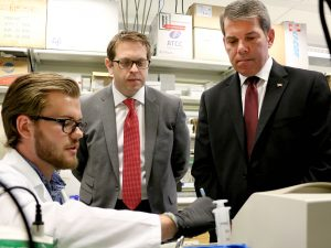 Brock University student Aindriu Maguire, an NSERC Undergraduate Student Research Awardee, explains cell research to Members of Parliament Vance Badawey (Niagara Centre), right, and Chris Bittle (St. Catharines) in the lab of Assistant Professor of Health Sciences Adam MacNeil during a tour at Brock University Tuesday, June 28.