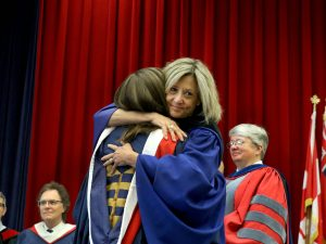 Retiring Registrar Barb Davis hugs her daughter Hannah Anderson after handing her an honours bachelor of arts degree during convocation Wednesday.