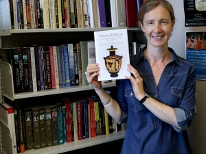 Classics Professor Allison Glazebrook holds a copy of her new book Houses of Ill Repute: The Archaeology of Brothels, Houses, and Taverns in the Greek World.