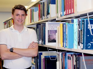 Kyle Fraser stands in a library