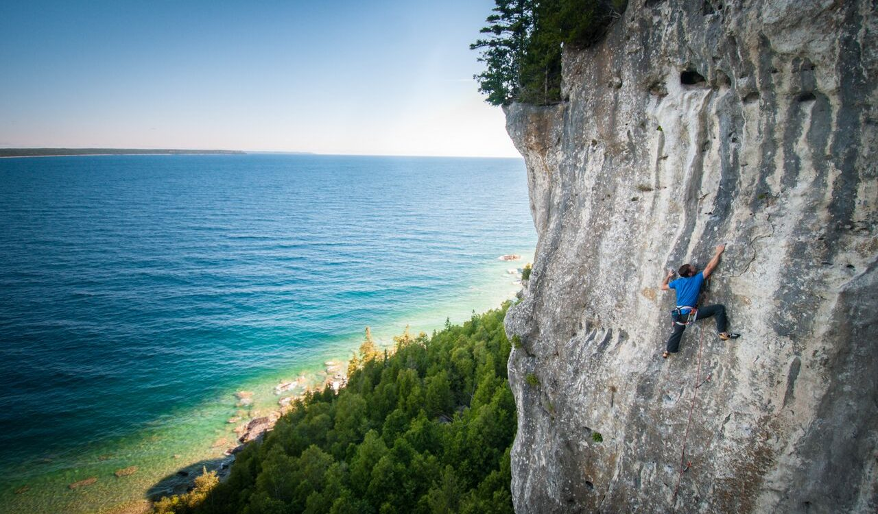 Aaron Brouwers climbing on a rock face near a lake