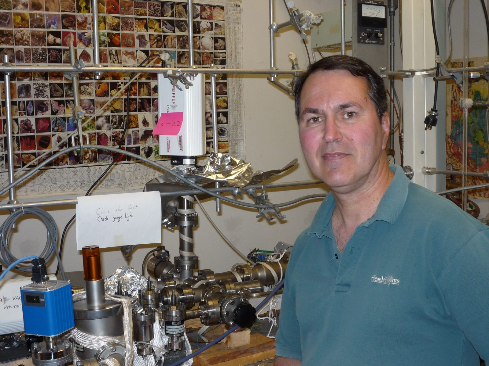 Earth Sciences Professor Nigel Blamey in front of a machine built to measure oxygen in prehistoric air.