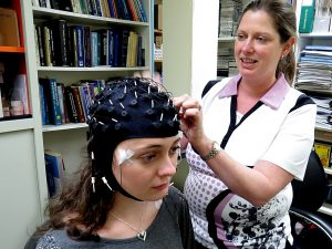 Psychology Professor Kimberly Cote attaches a sleep monitor to grad student Kari Lustig.