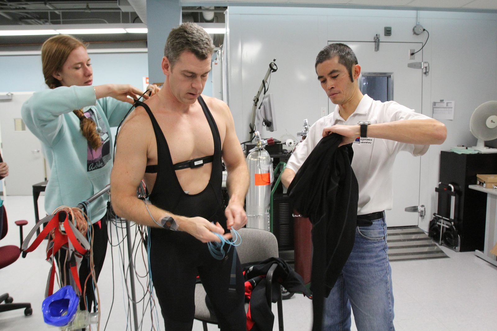 Stephen Cheung, right, and research assistant Tamara Zwaan prepare Mike Taber for a bicycle ride in Cheung's lab at Brock University.