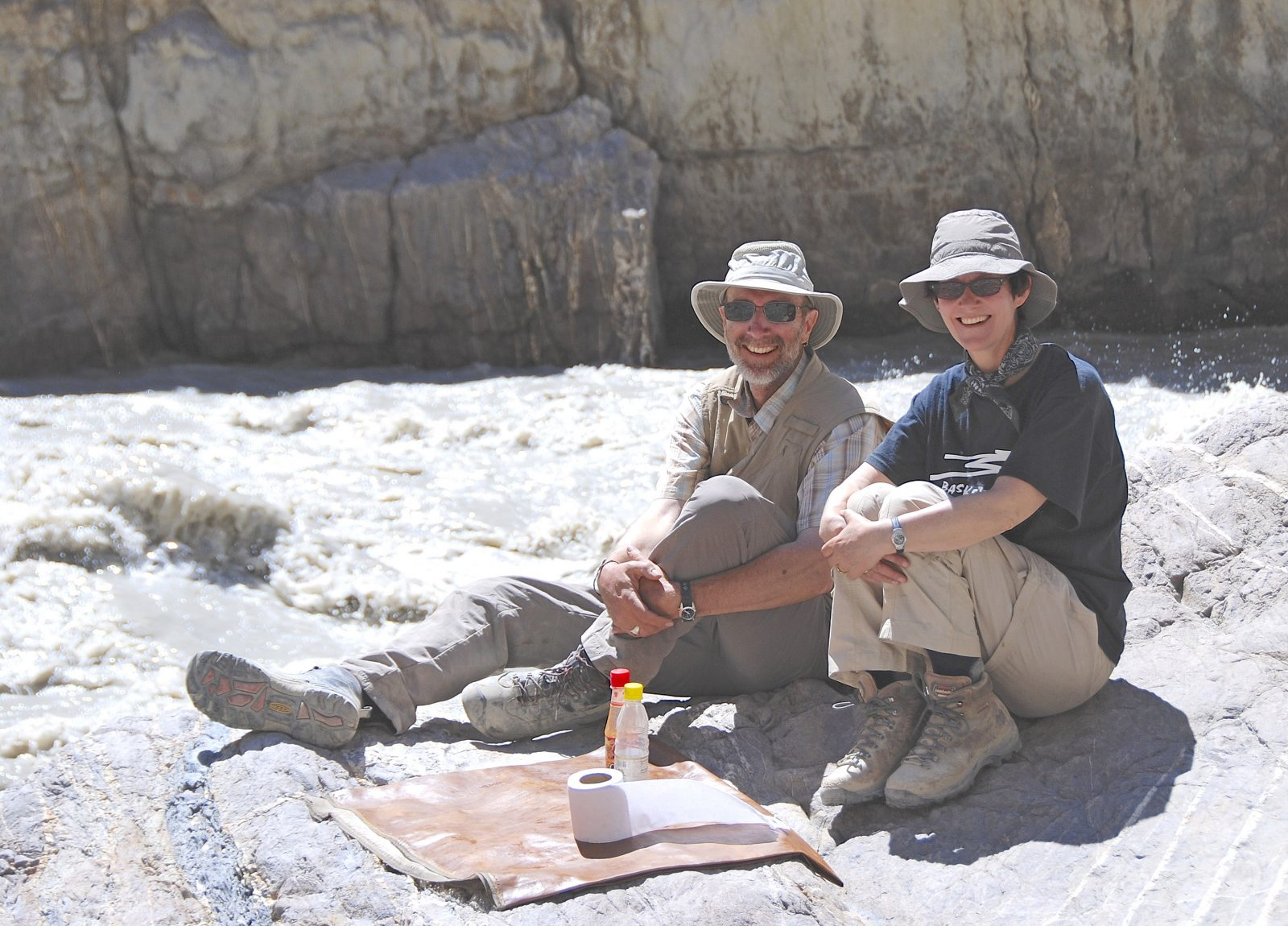 David Butz and Nancy cook sitting on the ground in front of rocks in Pakistan